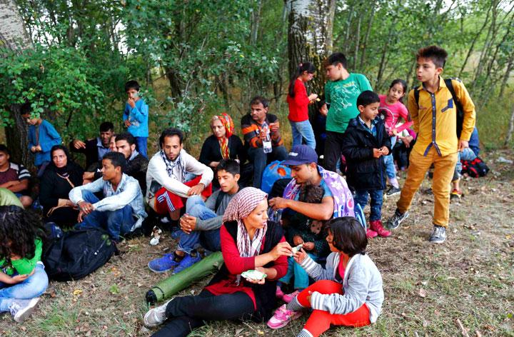 Группа мигрантов из разных стран отдыхают на обочине дороги после пересечения границы Сербии