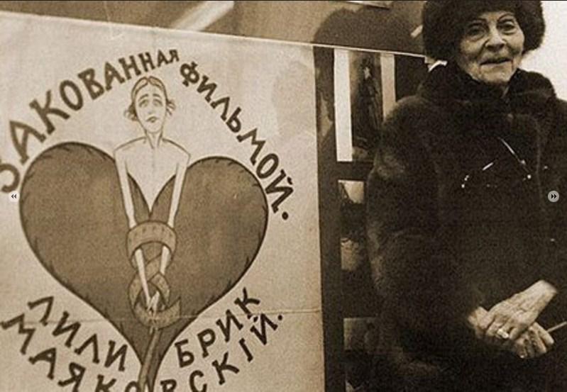 """Лиля Юрьевна в 1970-х годах - рядом плакат целиком несохранившейся ленты 1918 года """"Скованная фильмой"""", в которой снялись Брик и Маяковский. Сюжет этого фильма позже использовал Вуди Аллен в своем фильме «Пурпурная роза Каира»."""