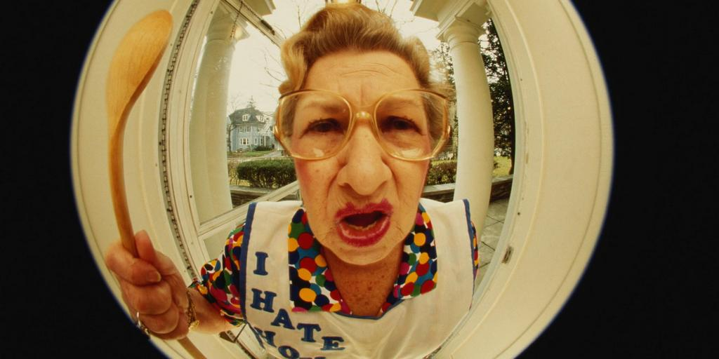 Mature woman standing outside front door, waving spoon (fish-eye)
