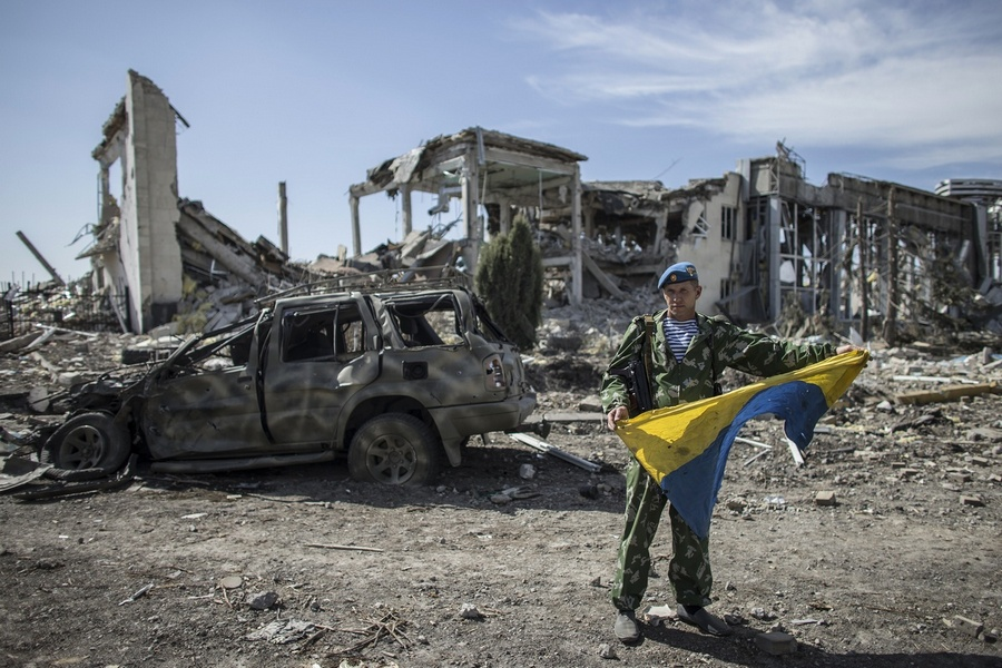 Yakut, an ex-Russian paratrooper, displays a captured Ukrainian flag at the destroyed airport in Luhansk